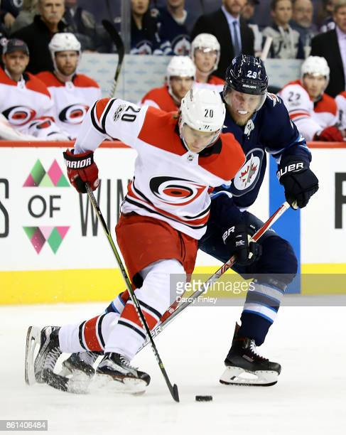 Sebastian Aho of the Carolina Hurricanes plays the puck away from Patrik Laine of the Winnipeg Jets during first period action at the Bell MTS Place...