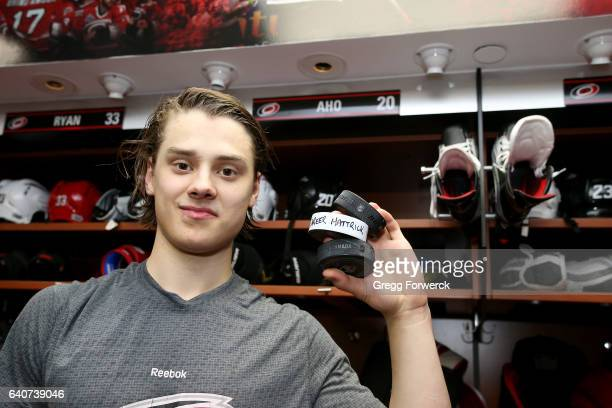 Sebastian Aho of the Carolina Hurricanes poses with 3 pucks as he celebrates his first NHL hat trick during an NHL game against the Philadelphia...