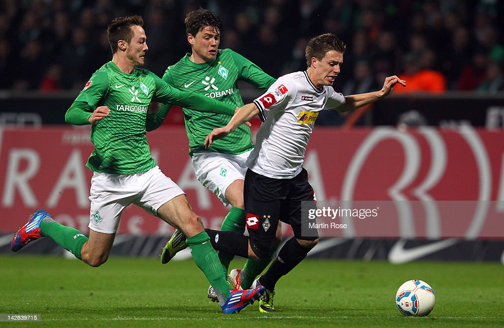 <a gi-track='captionPersonalityLinkClicked' href=/galleries/search?phrase=Sebastian+Boenisch&family=editorial&specificpeople=632472 ng-click='$event.stopPropagation()'>Sebastian Boenisch</a> (C) of Bremen fouls Patrick Hermann (R) of Moenchengladbach during the Bundesliga match between SV Werder Bremen and Borussia Moenchengladbach at Weser Stadium on April 10, 2012 in Bremen, Germany.