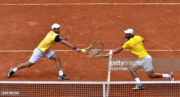 Sebastian Cabal and Alejandro Falla of Colombia in action during a doubles match against Santiago Giraldo of Colombia as part of Davis Cup at La...