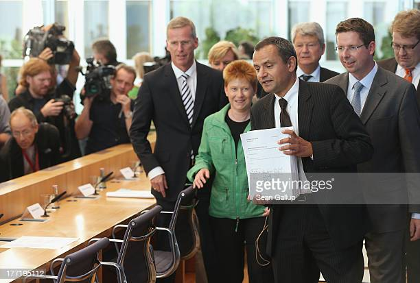 Sebastian Edathy chairman of the Bundestag commission investigating the NSU murder series holds up the commission's 1300page report together with...