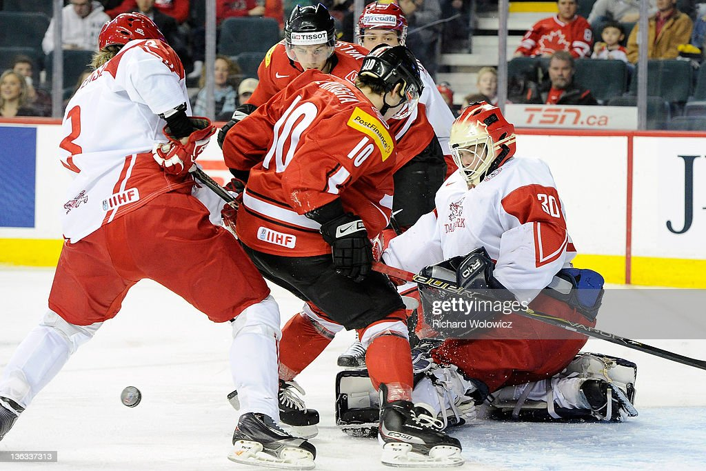 Sebastian Feuk #30 of Team Denmark watches the rebounding puck in front of teammate Jannik Christensen #3 and Alessio Bertaggia #10 of Team Switzerland during a relegation game at the 2012 World Junior Hockey Championships at the Saddledome on January 2, 2012 in Calgary, Alberta, Canada.