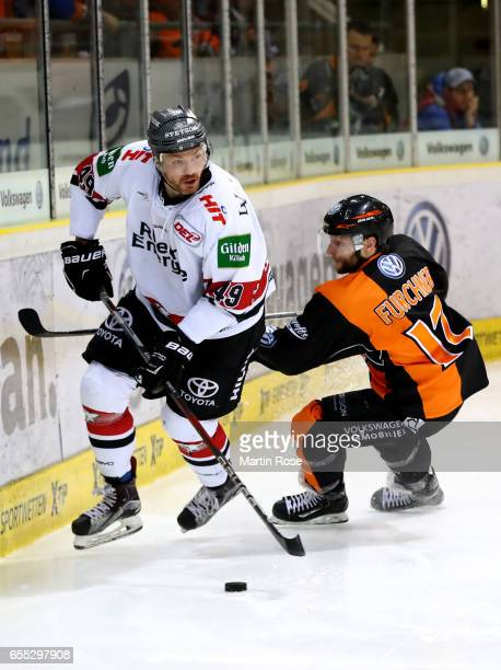 Sebastian Furchner of Wolfsburg and Alexandre Bolduc of Koeln battle for the puck during the DEL Playoffs quarter finals Game 6 between Grizzlys...
