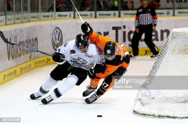 Sebastian Furchner of Wolfsburg and Jesse Blacker of Nuernberg battle for the puck during the DEL Playoffs semi finals Game 4 between Grizzlys...