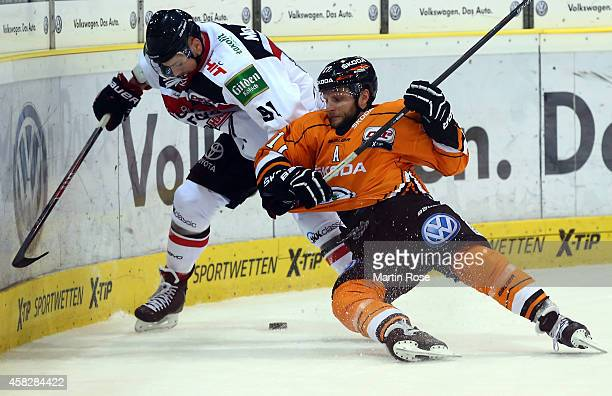 Sebastian Furchner of Wolfsburg and Moritz Mueller of Koeln battle for the puck during the DEL match between Grizzly Adams Wolfsburg and Koelner Haie...