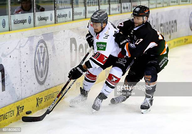 Sebastian Furchner of Wolfsburg and Moritz Mueller of Koeln battle for the puck during the DEL match between Grizzly Wolfsburg and Koelner Haie at...