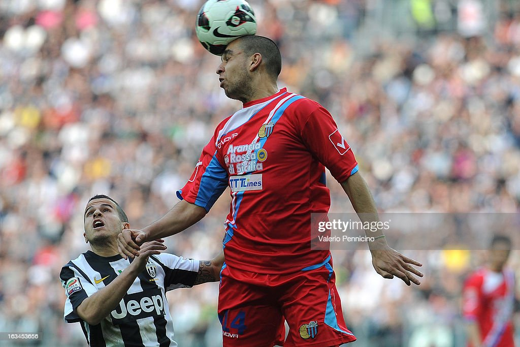 Sebastian Giovinco (L) of FC Juventus goes up with Giuseppe Bellusci of Calcio Catania during the Serie A match between FC Juventus and Calcio Catania at Juventus Arena on March 10, 2013 in Turin, Italy.