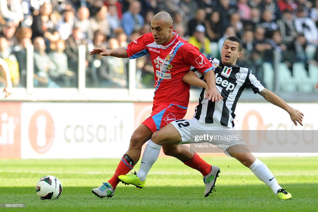Sebastian Giovinco (R) of FC Juventus is challenged by Sergio Bernardo Almiron of Calcio Catania during the Serie A match between FC Juventus and Calcio Catania at Juventus Arena on March 10, 2013 in Turin, Italy.