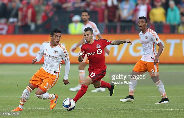 Sebastian Giovinco of Toronto FC chases Leonel Miranda of the Houston Dynamo during an MLS soccer game at BMO Field on May 10 2015 in Toronto Ontario...