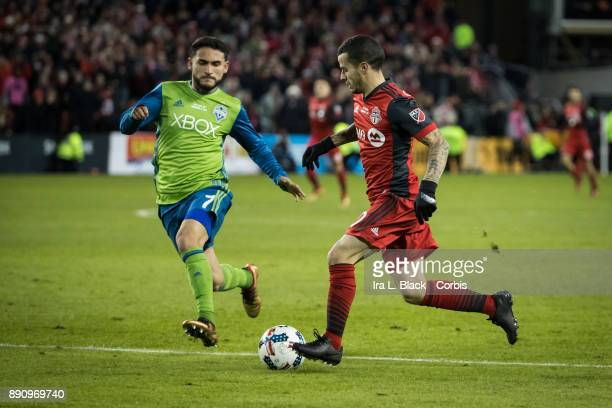 Sebastian Giovinco of Toronto FC tries to drive past Cristian Roldan of Seattle Sounders during the 2017 Audi MLS Championship Cup match between...