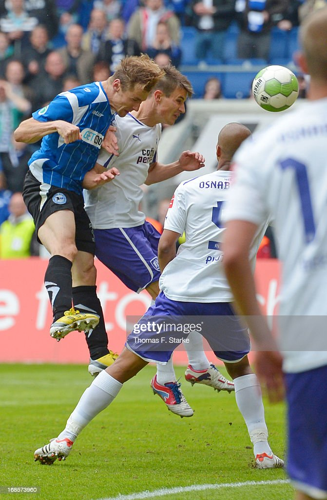 Sebastian Hille (L) of Bielefeld heads the winning goal against Nils Fischer (C) and David Pisot (back R) of Osnabrueck during the Third League match between Arminia Bielefeld and VfL Osnabrueck at Schueco Arena on May 11, 2013 in Bielefeld, Germany.