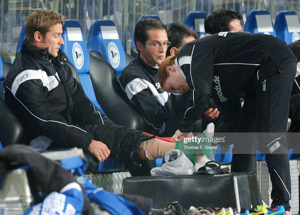 Sebastian Hille (L) of Bielefeld receives medical treatment during the DFB Cup match between Arminia Bielefeld and Bayer 04 Leverkusen at Schueco Arena on September 24, 2013 in Bielefeld, Germany.
