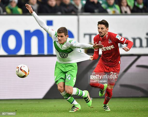 Sebastian Jung of VfL Wolfsburg is pulled back by Filip Mladenovic of Cologne during the Bundesliga match between VfL Wolfsburg and 1 FC Koeln at...