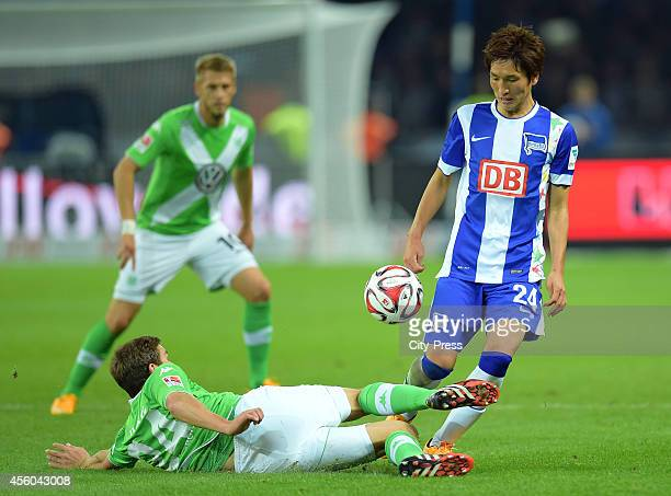 Sebastian Jung of VfL Wolfsburg tackles Genki Haraguchi of Hertha BSC during the Bundesliga match between Hertha BSC and VfL Wolfsburg on September...
