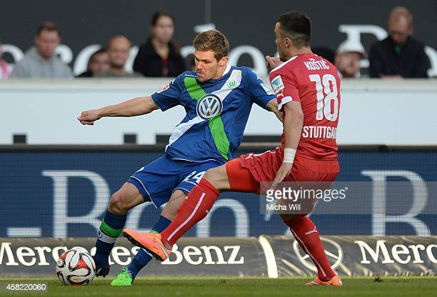 Sebastian Jung of Wolfsburg is challenged by Filip Kostic of Stuttgart during the Bundesliga match between VfB Stuttgart and VfL Wolfsburg at...