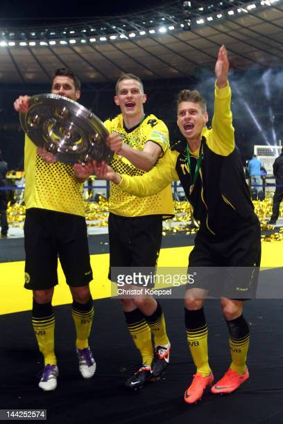 Sebastian Kehl Sven Bender and Lukasz Piszczek of Dortmund celebrate with the trophy after winning 52 the DFB Cup final match between Borussia...
