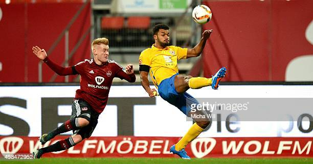 Sebastian Kerk of Nuernberg and Phil OfosuAyeh of Braunschweig tussle for the ball during the Second Bundesliga match between 1 FC Nuernberg and...