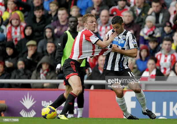 Sebastian Larsson of Sunderland and Hatem Ben Arfa of Newcastle challenge for the ball during the Barclays Premier League match between Sunderland...