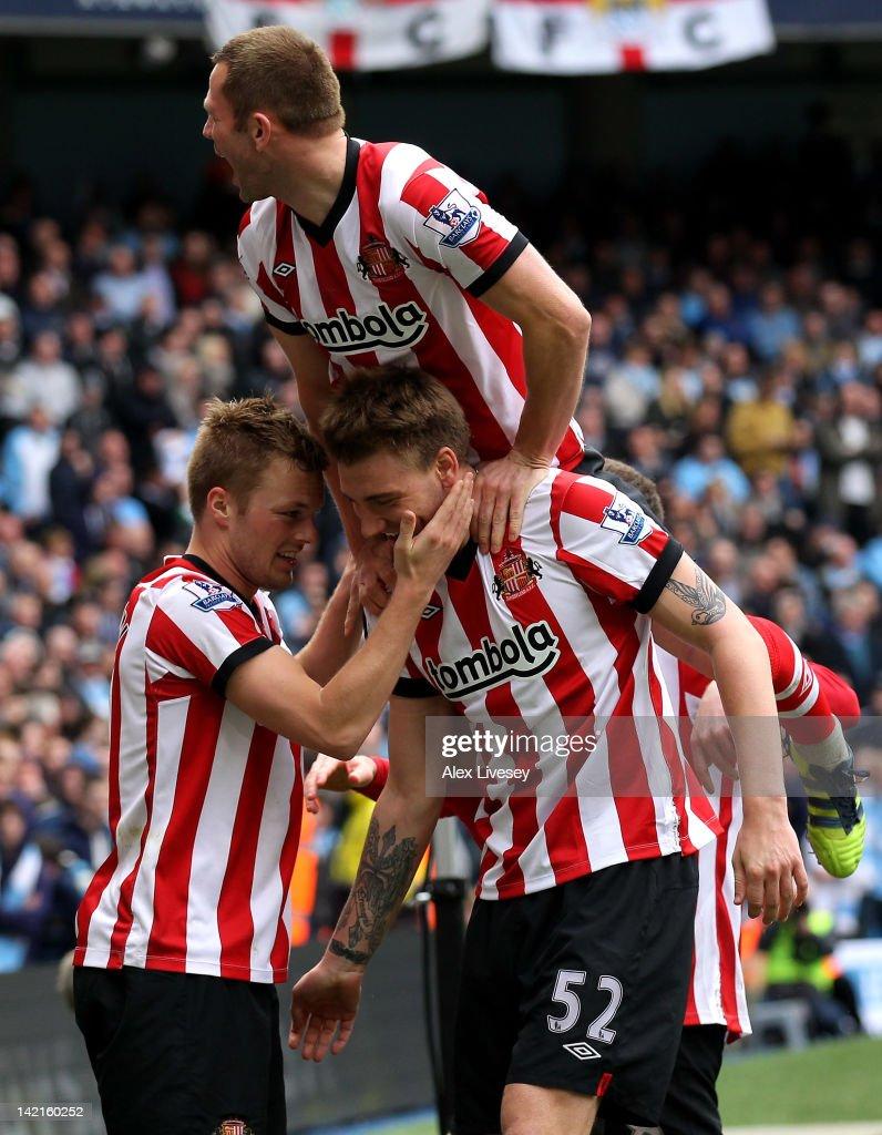 Sebastian Larsson of Sunderland celebrates scoring his team's third goal with Nickals Bendtner during the Barclays Premier League match between...