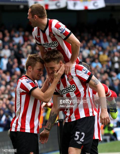 Sebastian Larsson of Sunderland celebrates scoring his team's third goal with Nickals Bendtner during the Barclays Premier League match between...