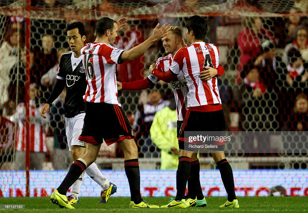 Sebastian Larsson of Sunderland celebrates with team-mates John O'Shea (L) & Ki Sung Yeung after scoring their second goal during the Capital One Cup fourth round match between Sunderland and Southampton at Stadium of Light on November 06, 2013 in Sunderland, England.