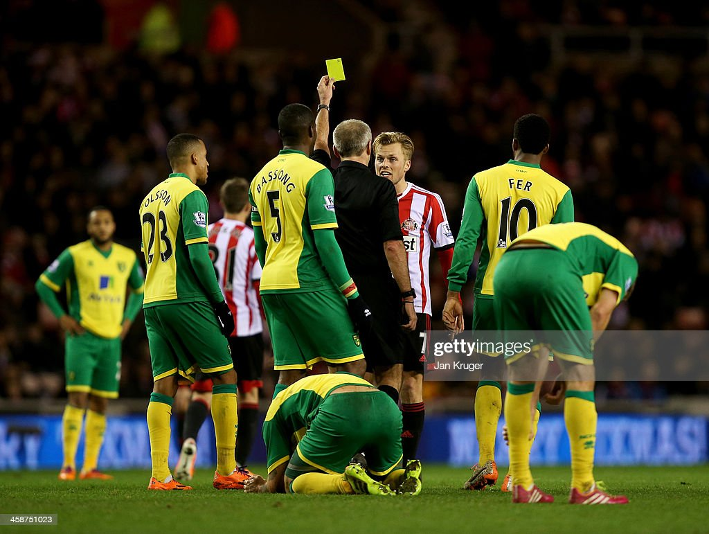 Sebastian Larsson of Sunderland is shown a yellow card by referee Martin Atkinson during the Barclays Premier League match between Sunderland and Norwich City at Stadium of Light on December 21, 2013 in Sunderland, England.