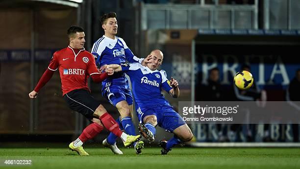 Sebastian Mrowca of SV WehenWiesbaden is challenged by Tim Siedschlag and Patrick Herrmann of Holstein Kiel during the 3 Liga match between SV...