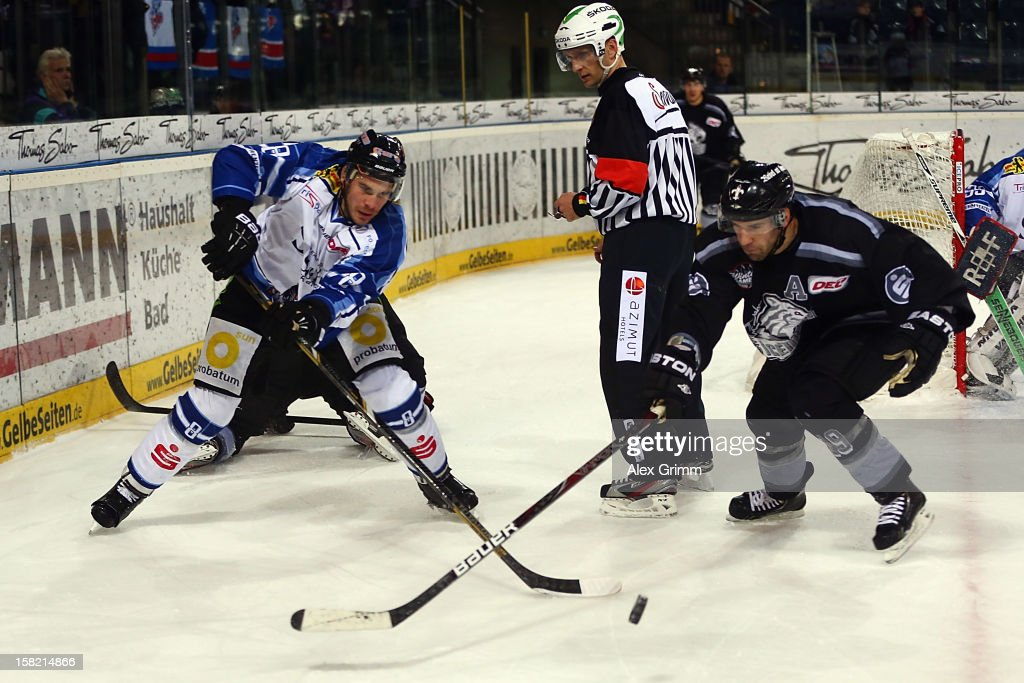 Sebastian Osterloh (L) of Straubing is challenged by Jason Jaspers of Ice Tigers during the DEL match between Thomas Sabo Ice Tigers and Straubing Tigers at Arena Nuernberger Versicherung on December 11, 2012 in Nuremberg, Germany.