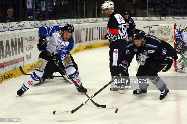 Sebastian Osterloh of Straubing is challenged by Jason Jaspers of Ice Tigers during the DEL match between Thomas Sabo Ice Tigers and Straubing Tigers...