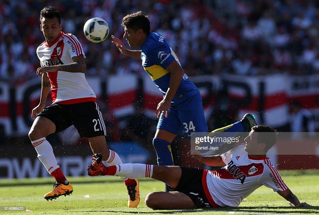 Sebastian Palacios, of Boca Juniors, (C) is tackled by Emanuel Mammana, of River Plate, during a match between River Plate and Boca Juniors as part of sixth round of Torneo Transicion 2016 at Monumental Antonio Vespucio Liberti Stadium on March 06, 2016 in Buenos Aires, Argentina.
