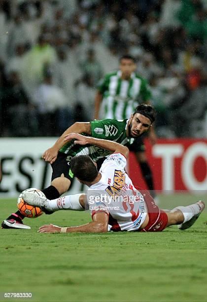 Sebastian Perez of Atletico Nacional vies for the ball with Martin Nervo of Huracan during a second leg match between Atletico Nacional and Huracan...