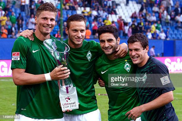 Sebastian Proedl Marko Arnautovic Mehmet Ekici and Zlatko Junuzovic of Bremen celebrate with the trophy after winning the LIGA total Cup 2012 final...