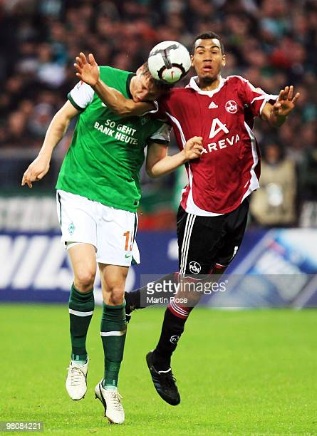 Sebastian Proedl of Bremen and Eric Maxim Choupo Moting of Nuernberg jump for a header during the Bundesliga match between Werder Bremen and 1 FC...