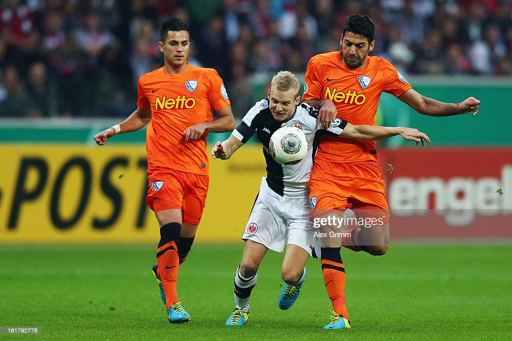 Sebastian Rode (C) of Frankfurt is challenged by Mirkan Aydin (R) and Danny Latza of Bochum during the DFB Cup second round match between Eintracht Frankfurt and VfL Bochum at Commerzbank-Arena on September 25, 2013 in Frankfurt am Main, Germany.