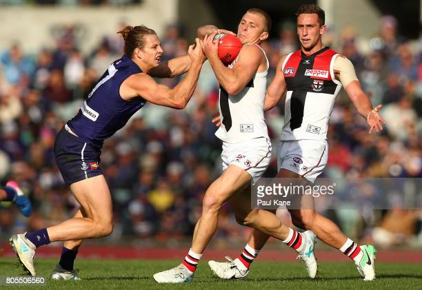 Sebastian Ross of the Saints attempts to break from a tackle by Nathan Fyfe of the Dockers during the round 15 AFL match between the Fremantle...