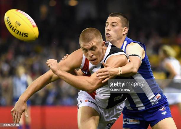 Sebastian Ross of the Saints handballs whilst being tackled by Nathan Hrovat of the Kangaroos during the round 13 AFL match between the North...