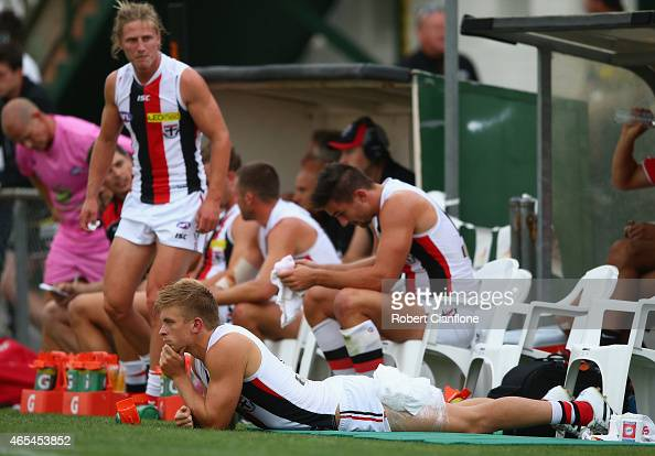 Sebastian Ross of the Saints looks on from the sidelinesafter he was injured during the NAB Challenge AFL match between the Essendon Bombers and the...