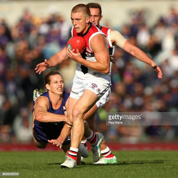 Sebastian Ross of the Saints slips from a tackle by Nathan Fyfe of the Dockers during the round 15 AFL match between the Fremantle Dockers and the St...