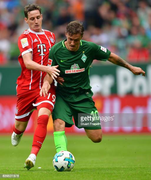 Sebastian Rudy of Bayern Muenchen fights for the ball with Max Kruse of Bremen during the Bundesliga match between SV Werder Bremen and FC Bayern...