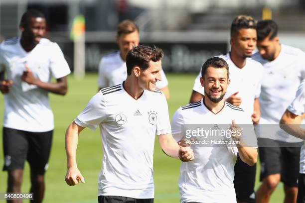 Sebastian Rudy of Germany smiles with his team mate Amin Younes during a training session of the German National team at RobertSchlienzStadion on...