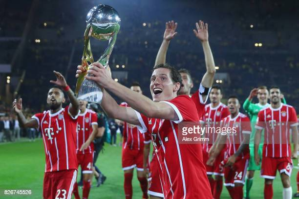 Sebastian Rudy of Muenchen celebrates with the trophy after his team won the DFL Supercup 2017 match between Borussia Dortmund and Bayern Muenchen at...