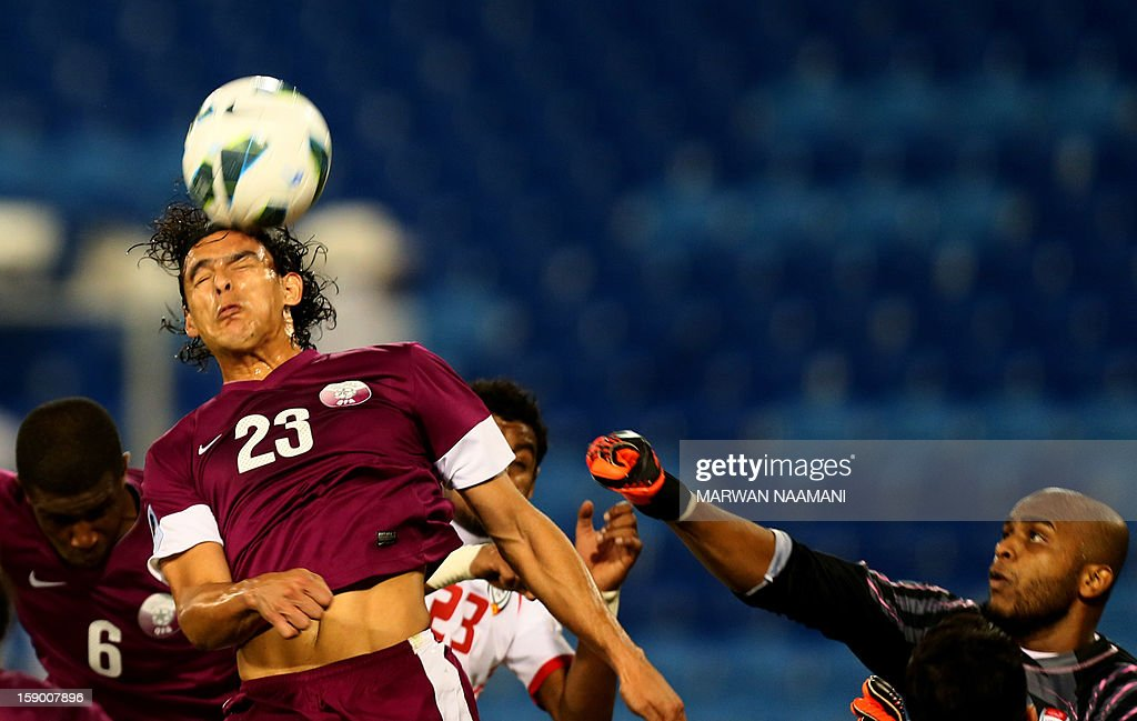 Sebastian Souria (L) of Qatar vies for the ball against Ali Hamid, the goal keeper of the United Arab Emirates during the two teams match in the 21st Gulf Cup in Manama, on January 5, 2013.