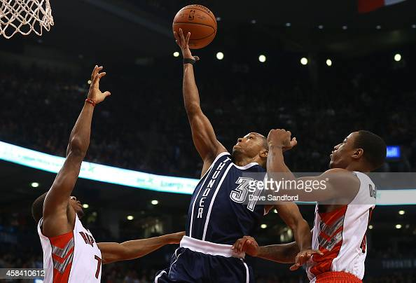 Sebastian Telfair of the Oklahoma City Thunder lays the ball up as he splits between Kyle Lowry of the Toronto Raptors and DeMar DeRozan of the...