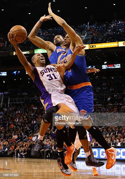 Sebastian Telfair of the Phoenix Suns attempts a shot against Marcus Camby and Chris Copeland of the New York Knicks during the NBA game at US...