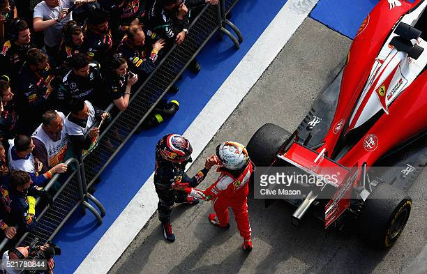 Sebastian Vettel of Germany and Ferrari and Daniil Kvyat of Russia and Red Bull Racing shake hands in parc ferme during the Formula One Grand Prix of...