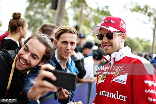 Sebastian Vettel of Germany and Ferrari arrives at the circuit and poses for a photo with a fan during practice ahead of the Australian Formula One...