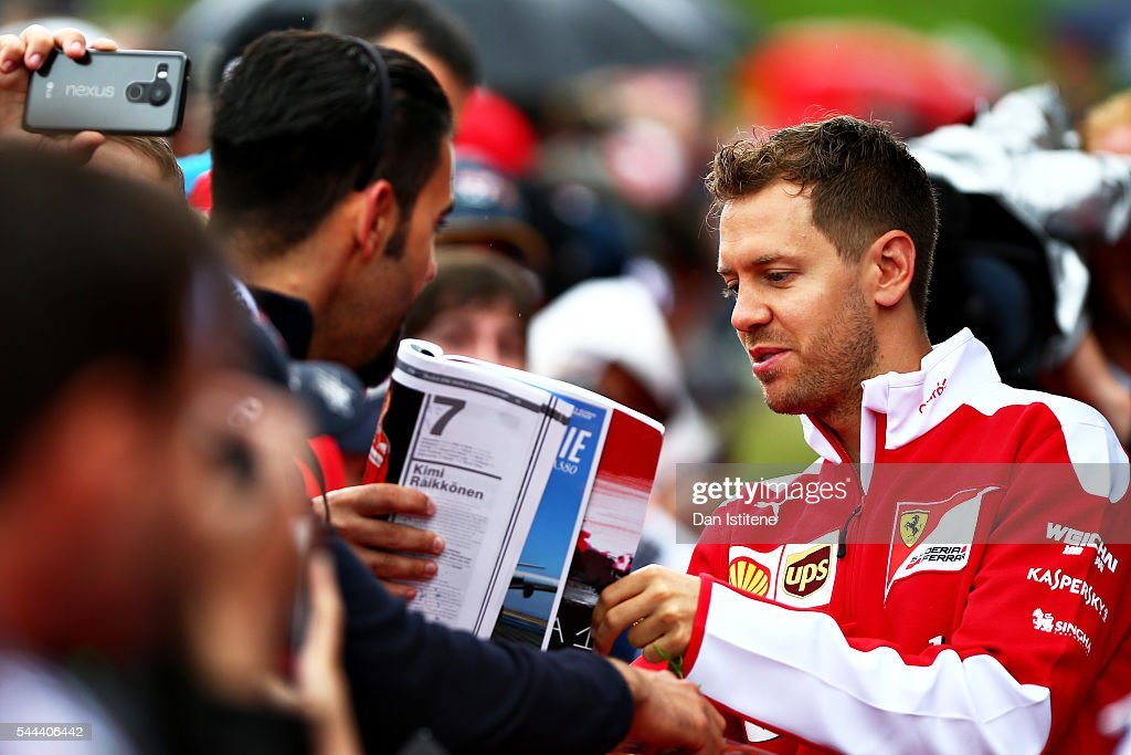 Sebastian Vettel of Germany and Ferrari arrives at the circuit and signs autographs for fans before the Formula One Grand Prix of Austria at Red Bull...