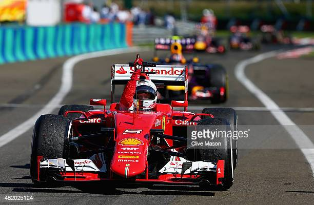 Sebastian Vettel of Germany and Ferrari celebrates as he approaches Parc Ferme after winning the Formula One Grand Prix of Hungary at Hungaroring on...
