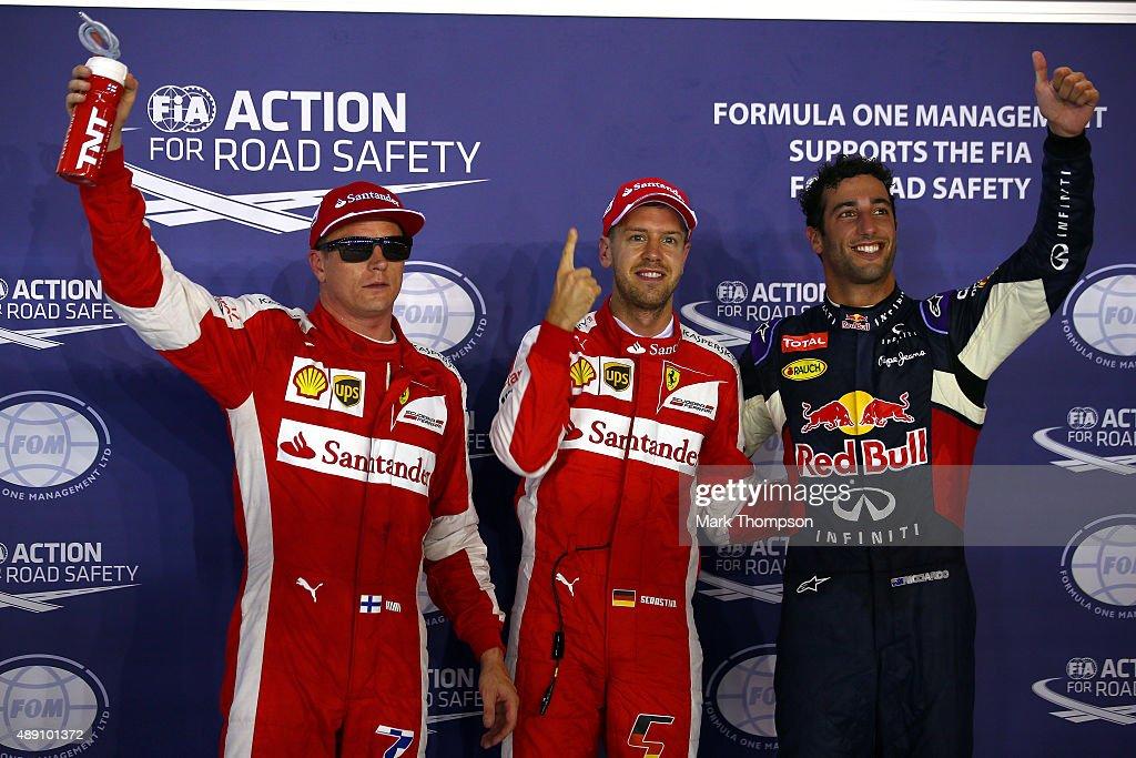 Sebastian Vettel of Germany and Ferrari celebrates in Parc Ferme next to Daniel Ricciardo of Australia and Infiniti Red Bull Racing and Kimi...