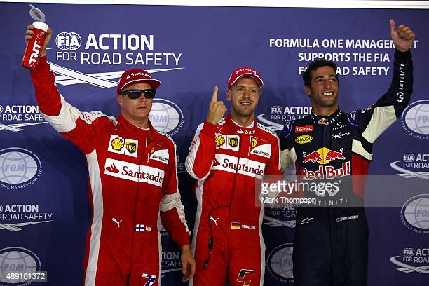 Sebastian Vettel of Germany and Ferrari celebrates in Parc Ferme next to Daniel Ricciardo of Australia and Infiniti Red Bull Racing and Kimi...